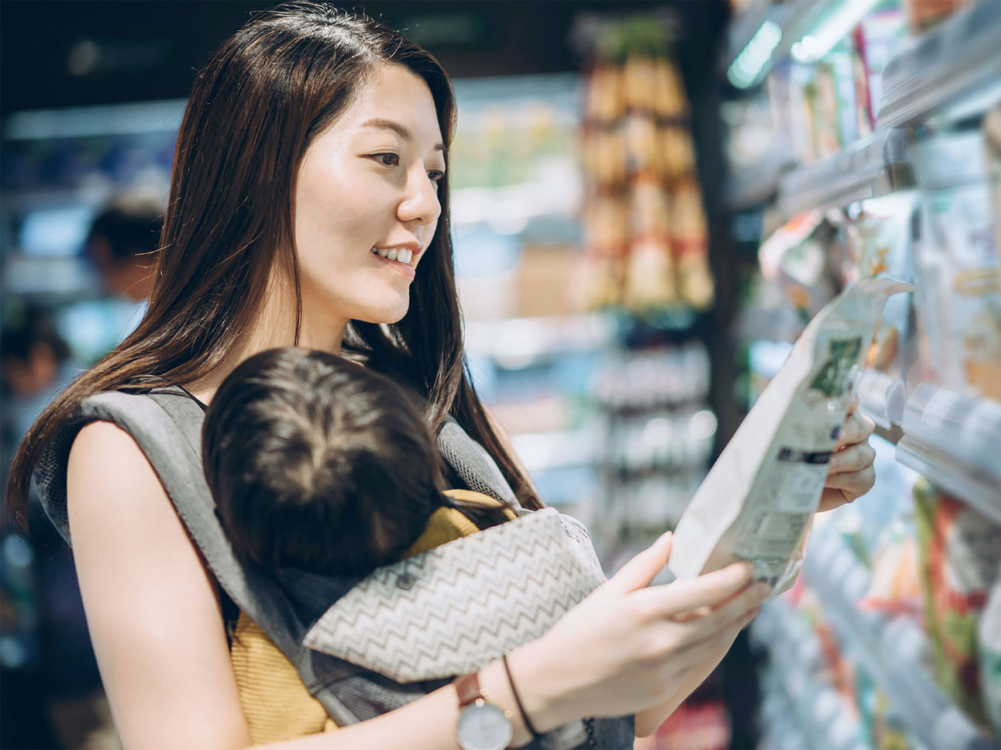 Asian mom with baby in grocery store looking at food label