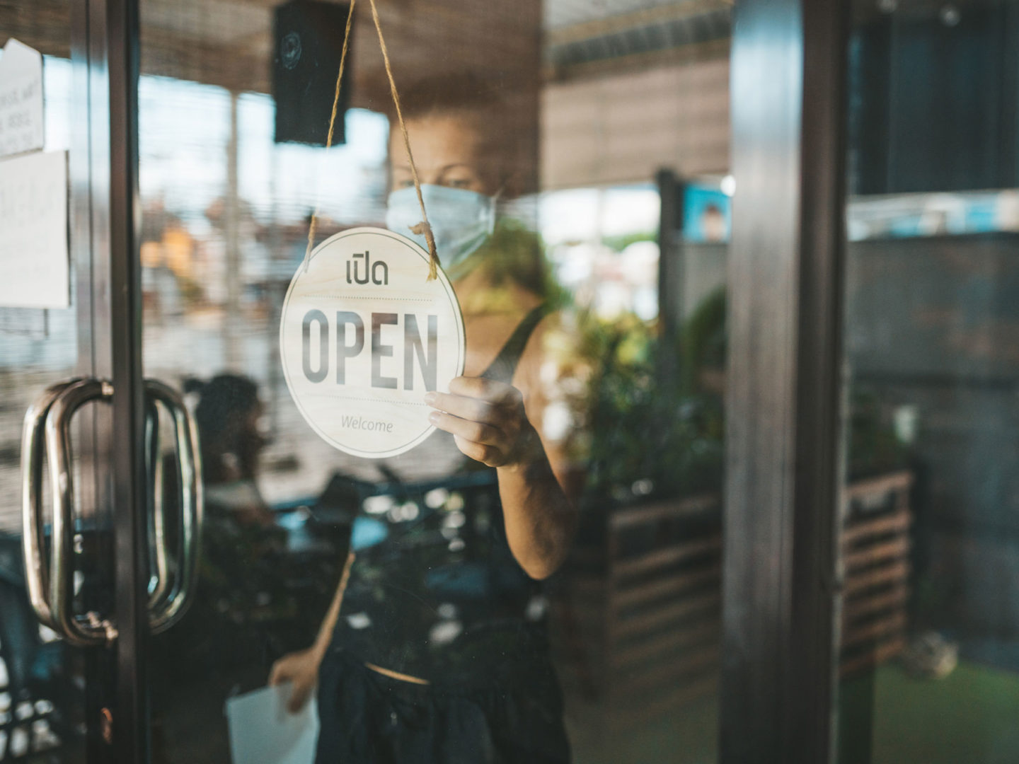 Business Owner Turning Sign to Open - Operating Your Business During COVID-19   NSF International