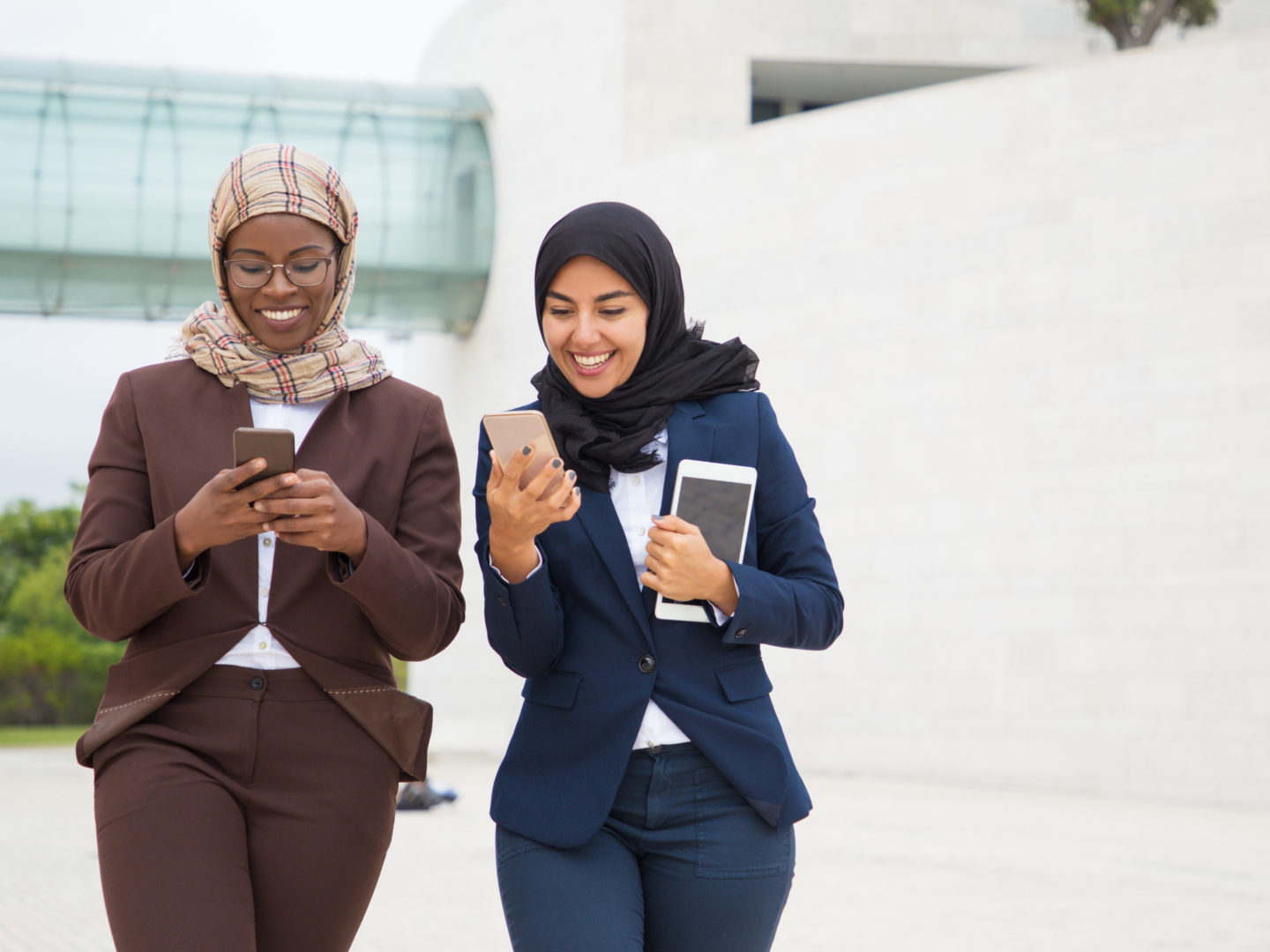 Business Women Smiling while Using Mobile Devices - Information Security Management Systems | NSF-ISR