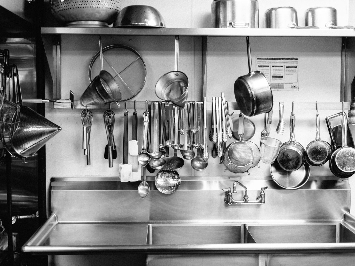 Pots, pans and tools hanging above commercial kitchen sink