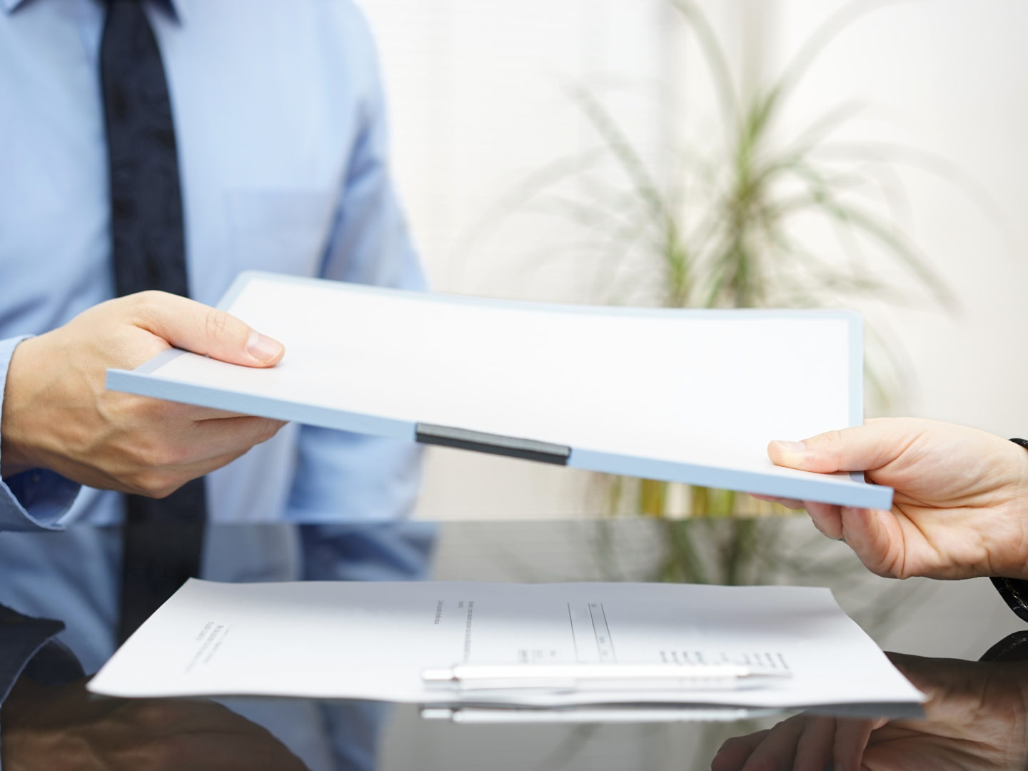 Two people exchanging documents