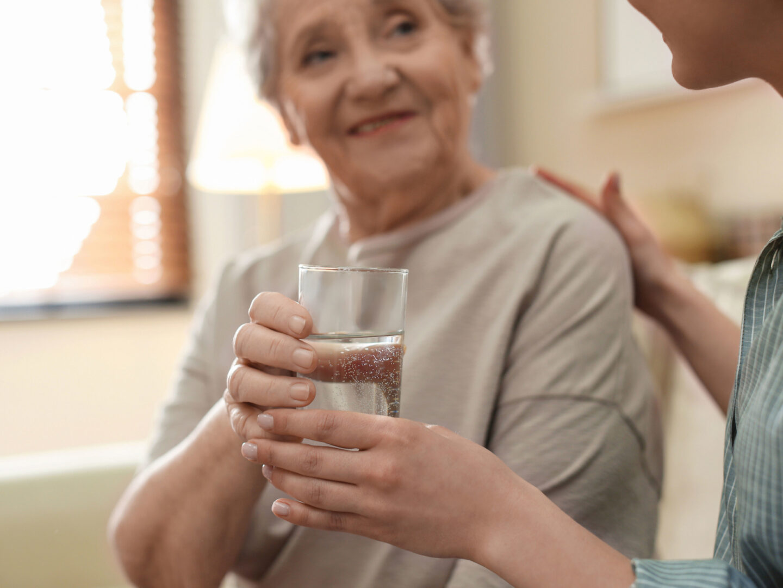 Elderly woman being handed water - Water Safety | NSF International