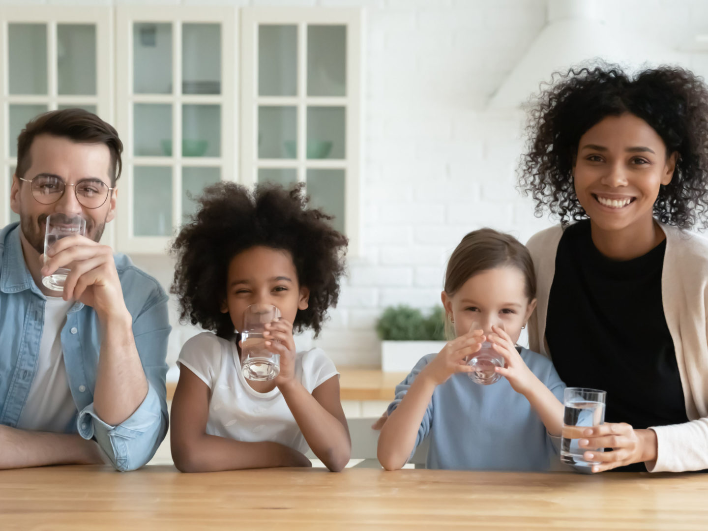 Family drinking water in kitchen - Water Filters, Reverse Osmosis and Water Treatment Systems | NSF International