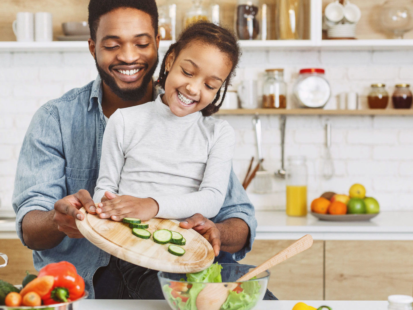 Girl and her father making salad together