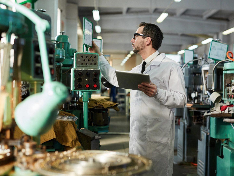 Man in Factory Reading Screen at Machine - Standards Portfolio   NSF International