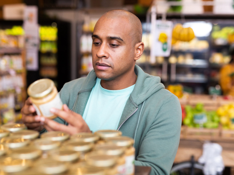 Man reading food label on a jar - Food Labeling | NSF International