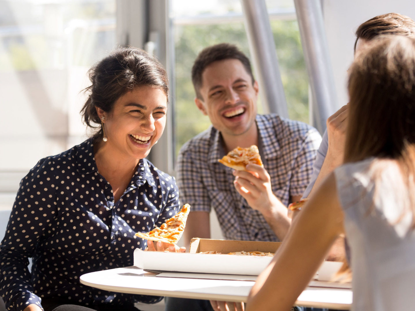 Indian woman laughing, eating pizza with colleagues in office
