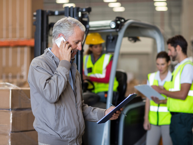Man reading clipboard in warehouse