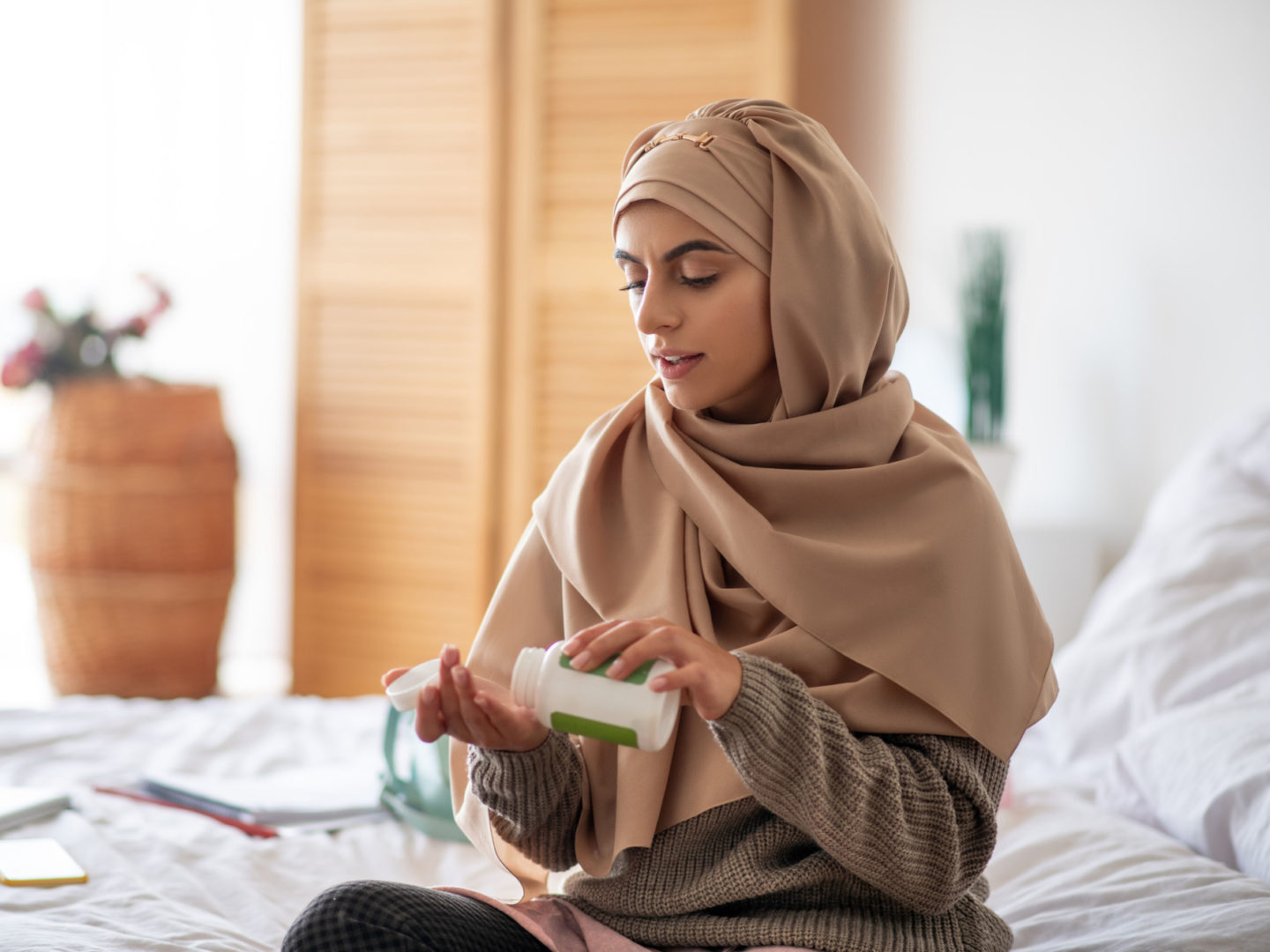 Woman on bed taking vitamin - Vitamins and Dietary Supplements | NSF International
