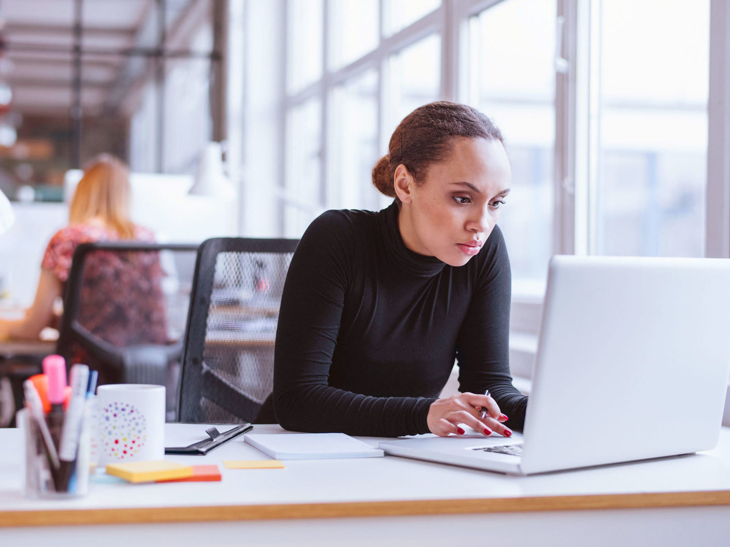 woman using laptop while sitting at her desk
