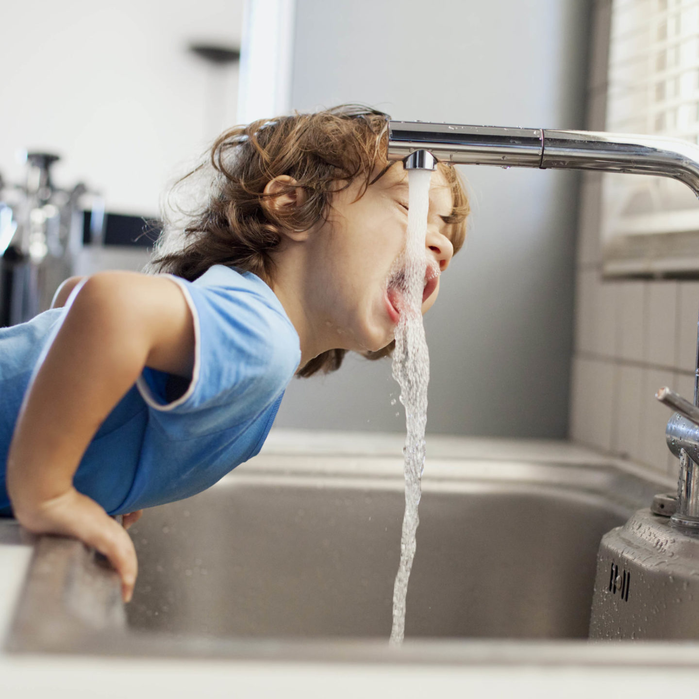 Boy drinking water from tap