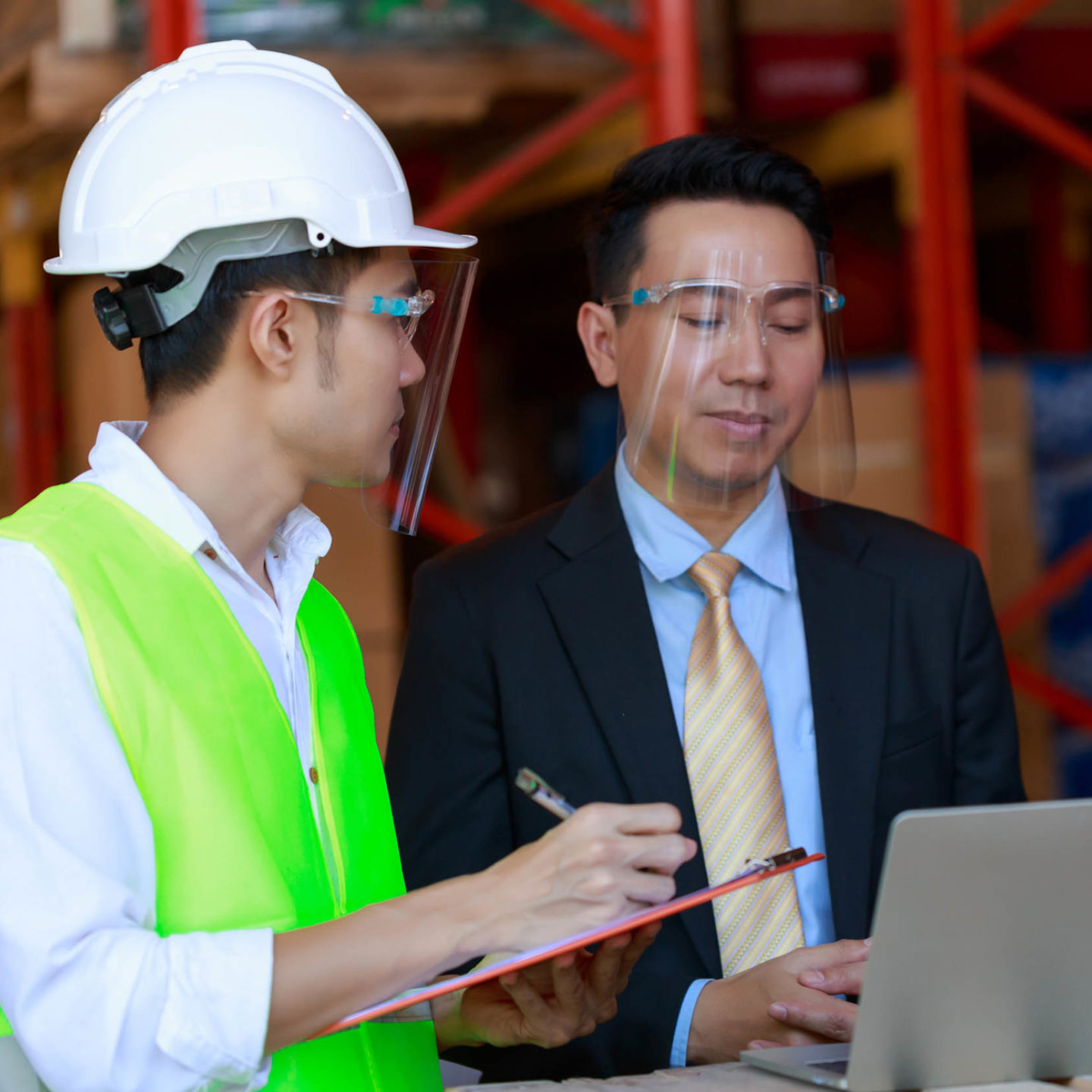 Business man and woman talking to construction worker while wearing face shields