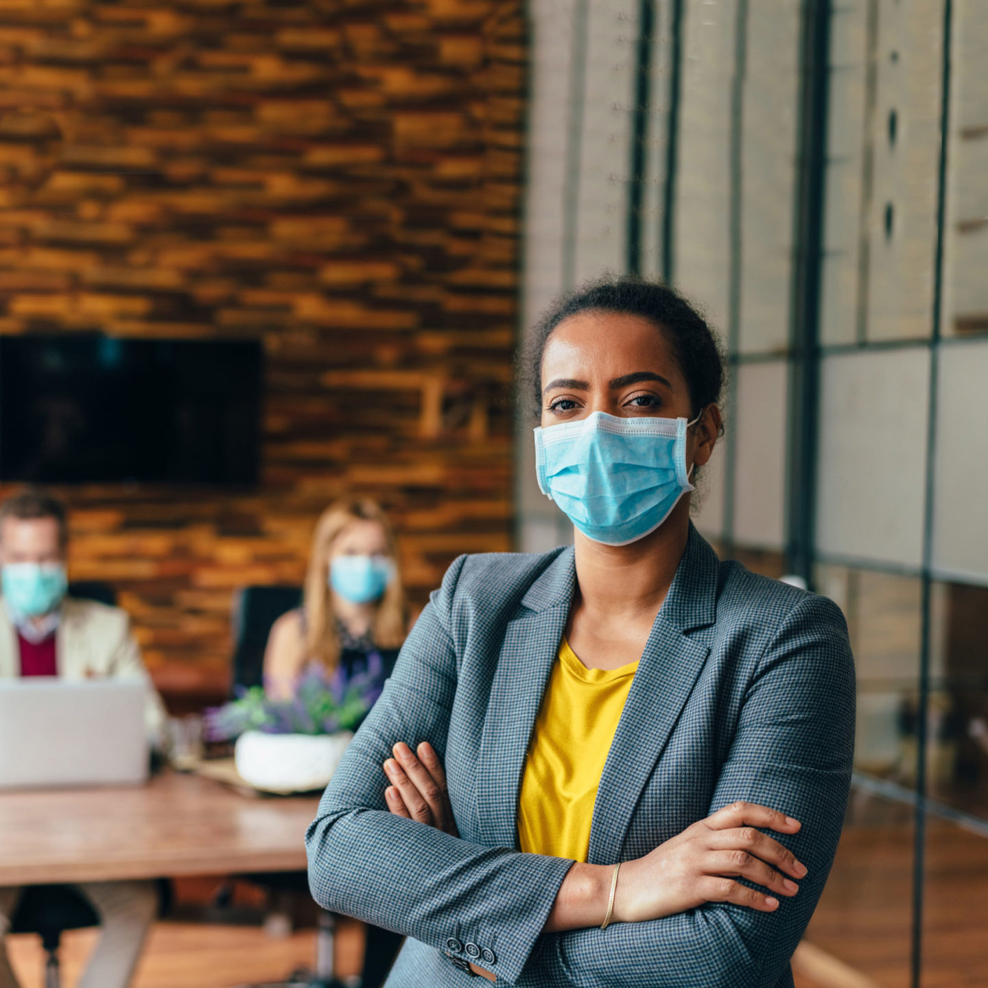 Business people masks in an office with businesswoman looking at camera