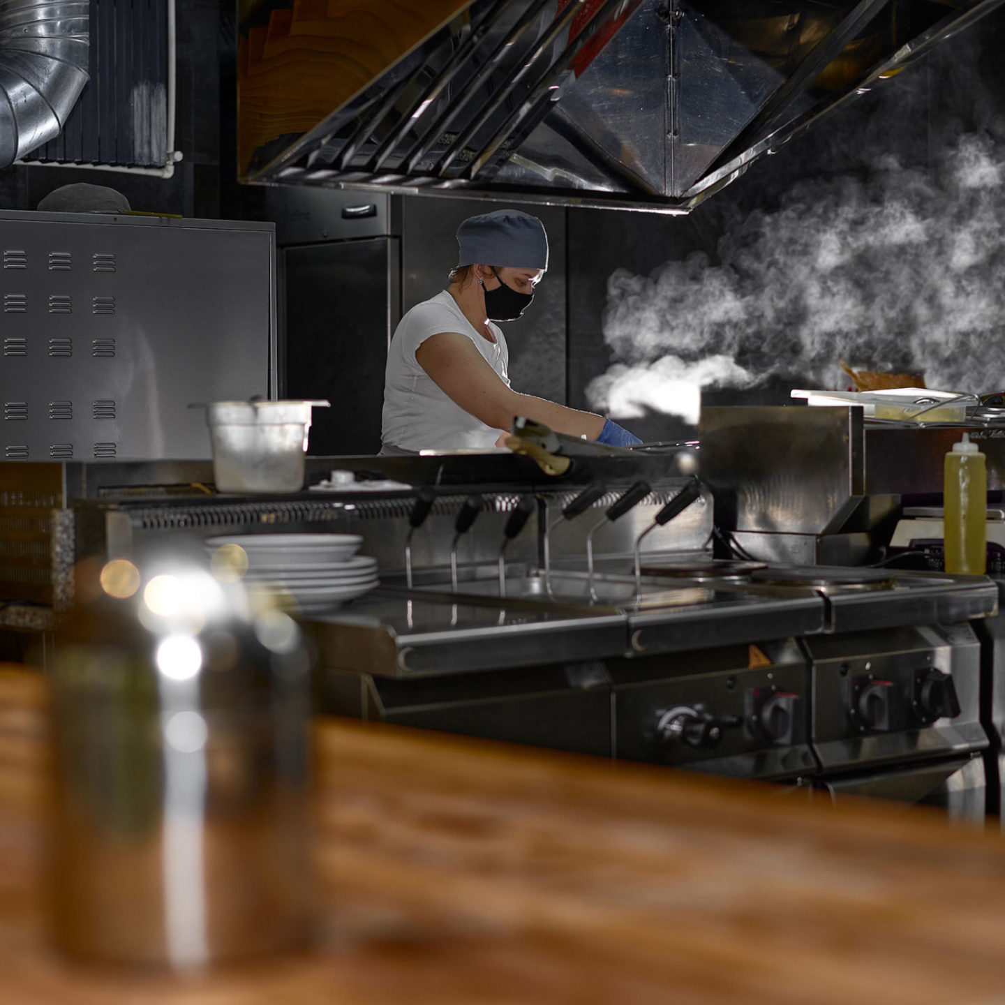 Chef wearing a face mask working in a restaurant kitchen