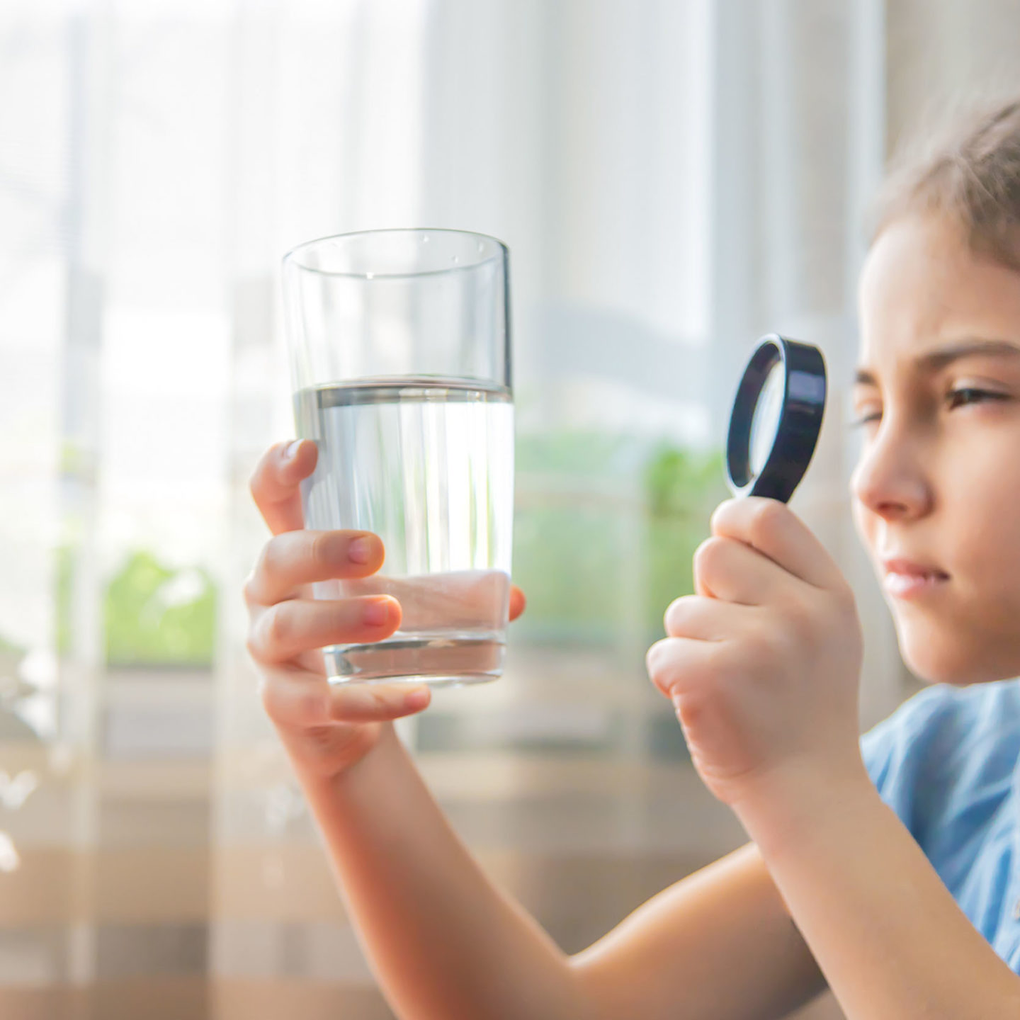 Child inspecting water glass - Prioritizing Children's Health: Revisions to EPA Rules and NSF Standards Help Reduce Lead in Drinking Water | NSF International