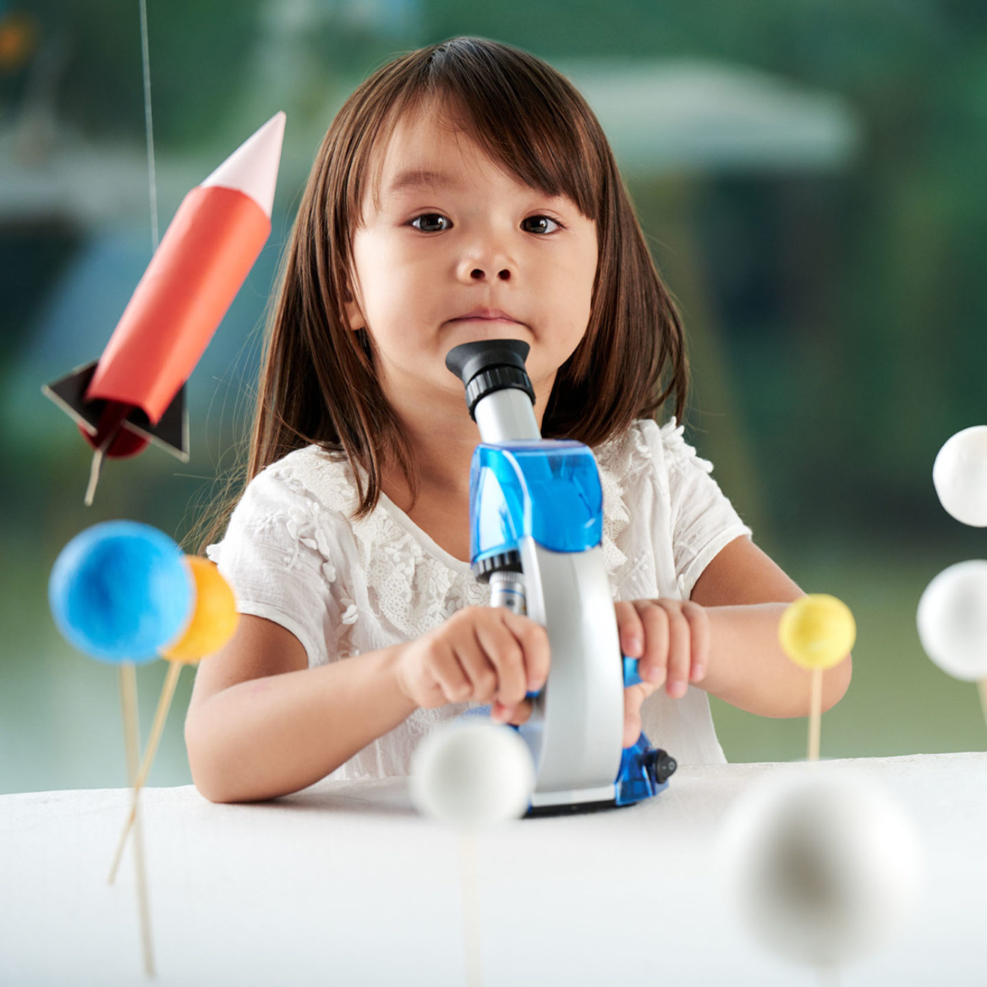 Child with microscope - Helping Clients Ensure Information Security | NSF International