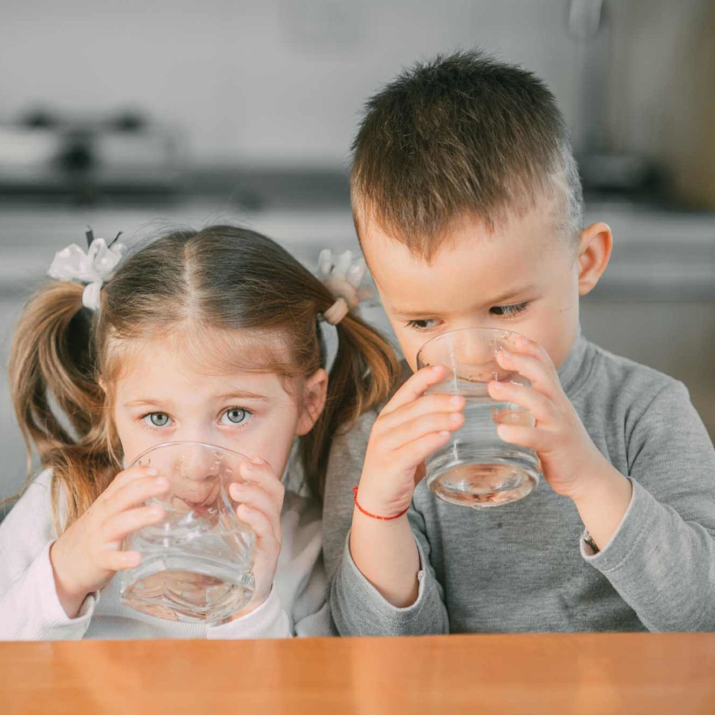 Children drinking water in kitchen - Finding the Best Water Filter for Your Home   NSF International