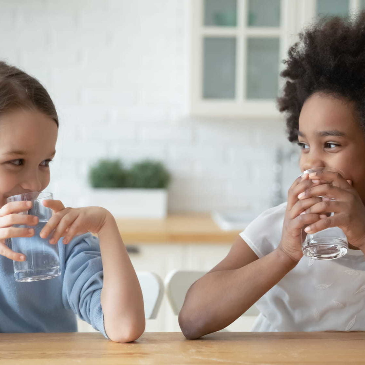 Smiling Little girls drinking pure mineral water - Water Well-being: Tips to Discover Lead in Your Drinking Water   NSF International