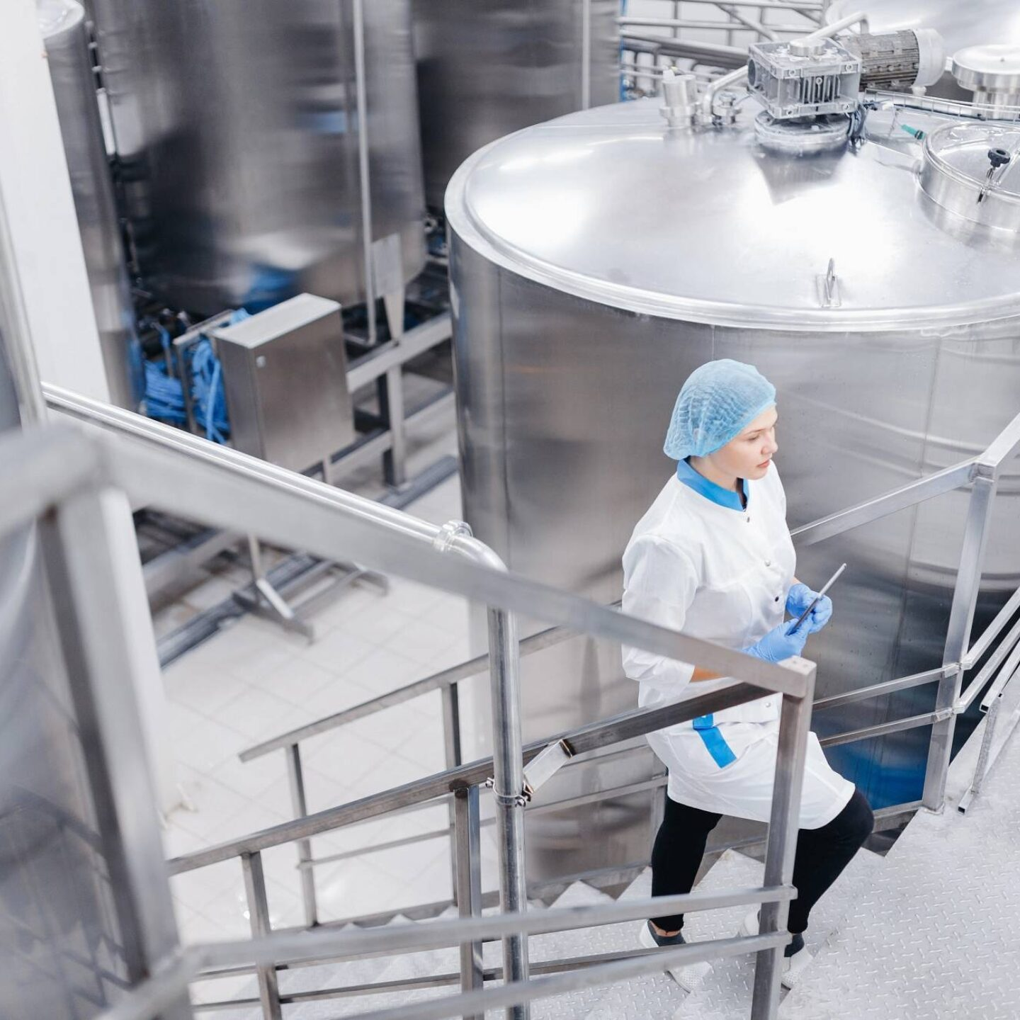 Female worker holding tablet at food factory - Steps to clean and sanitize food processing facility   NSF International