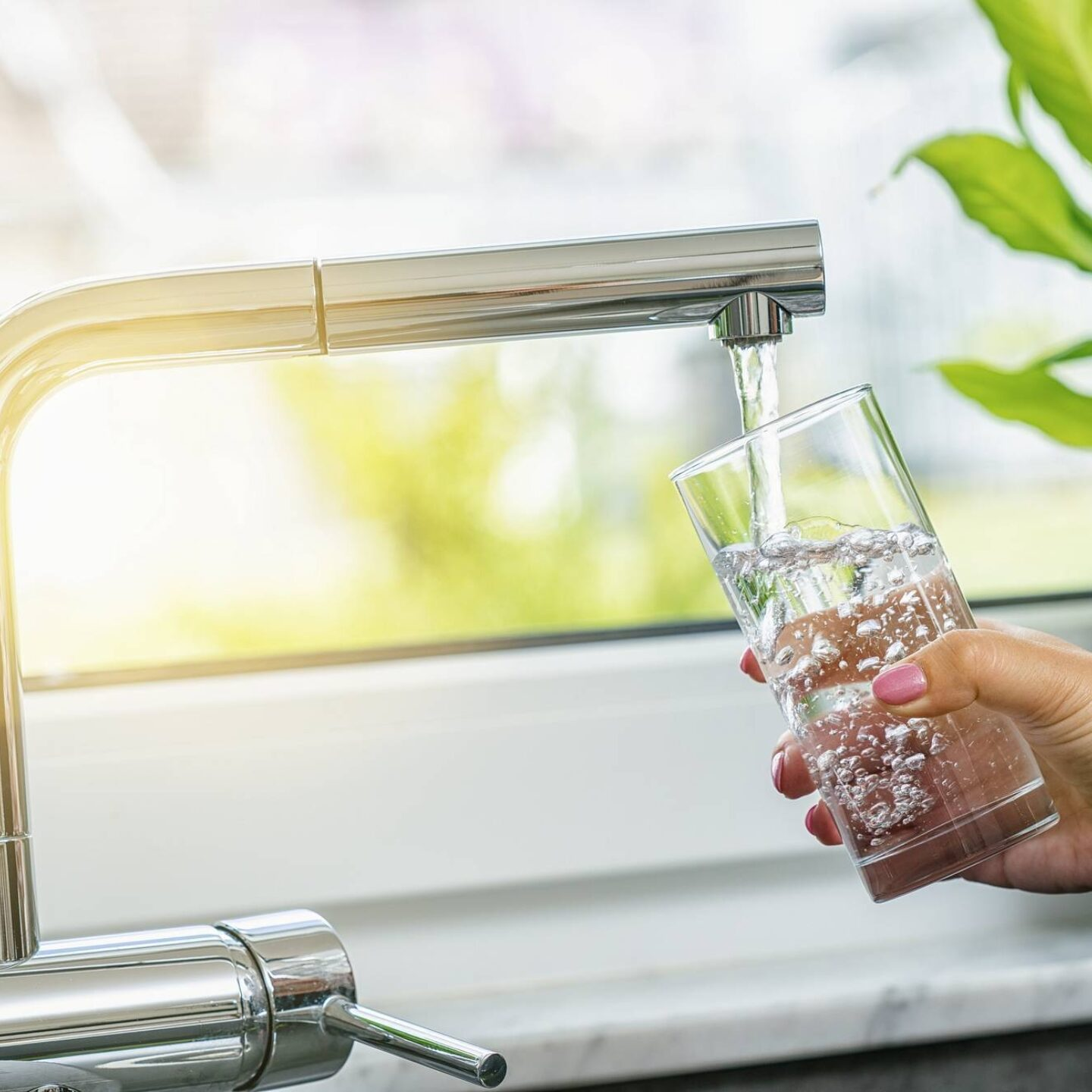Woman filling glass with water from a faucet - Learn How Reverse Osmosis Works Straight From The Experts   NSF International