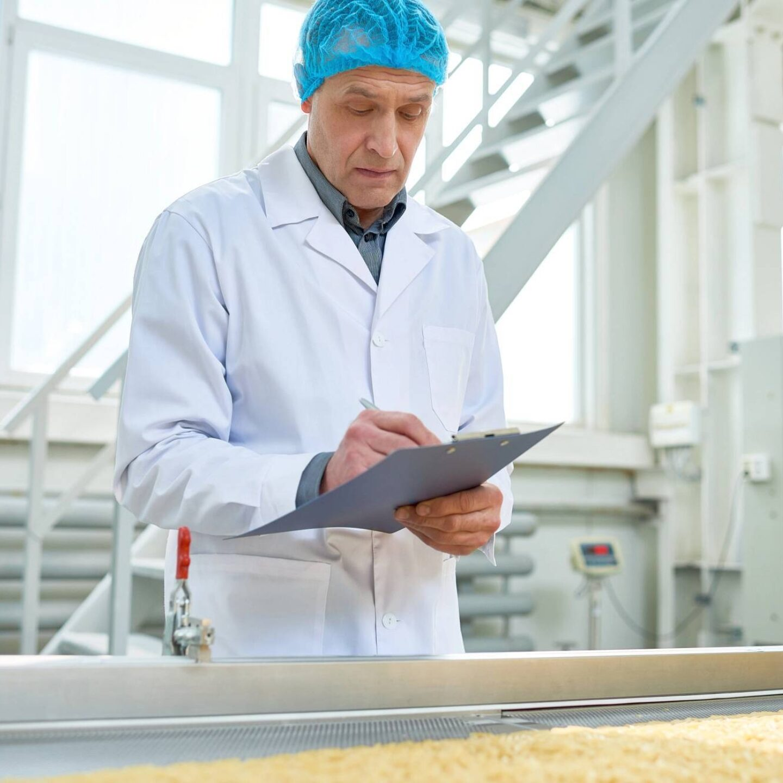 Senior worker in uniform supervising production of food - Food-Grade Lubricants Registrations | NSF International