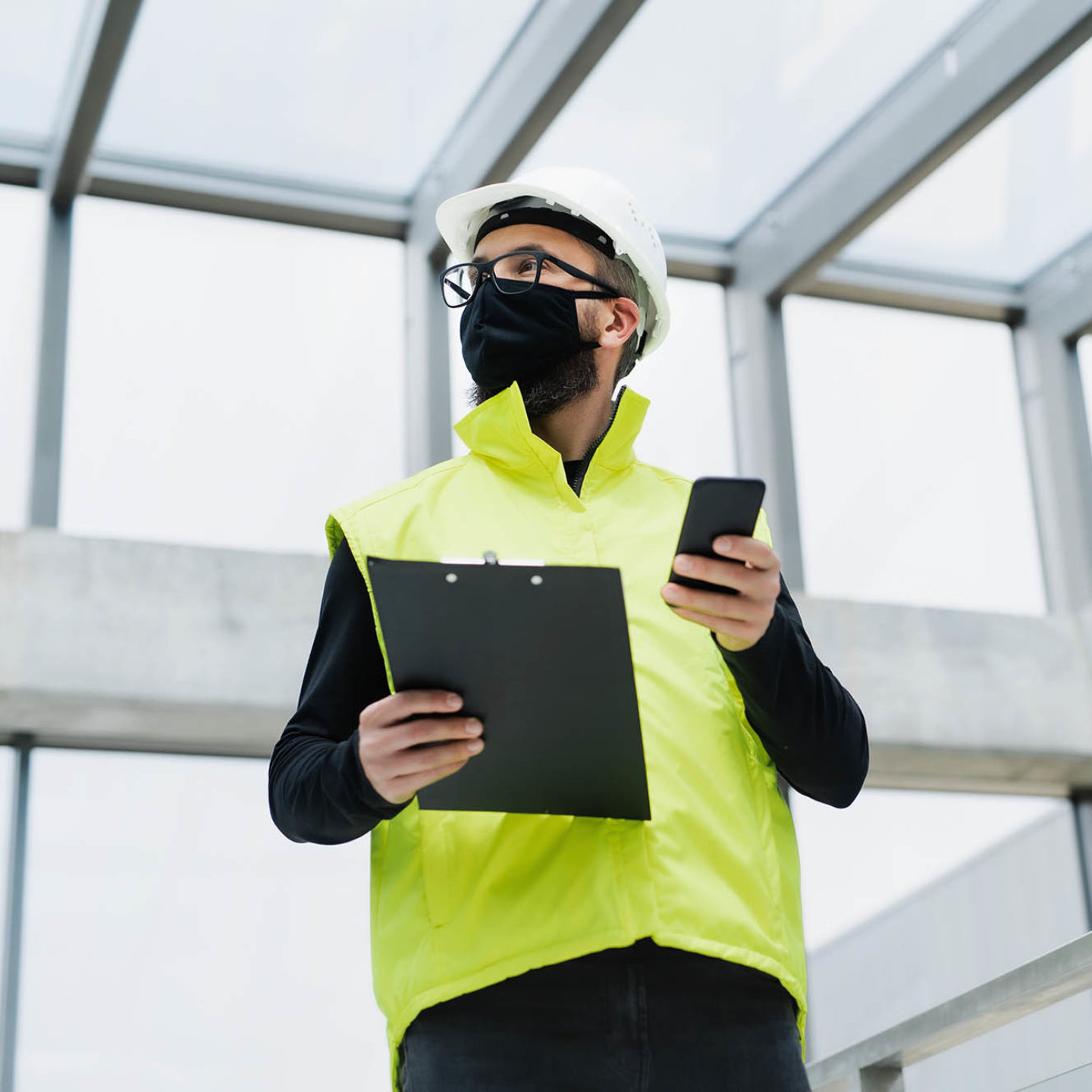 Man wearing mask, vest, and hardhat