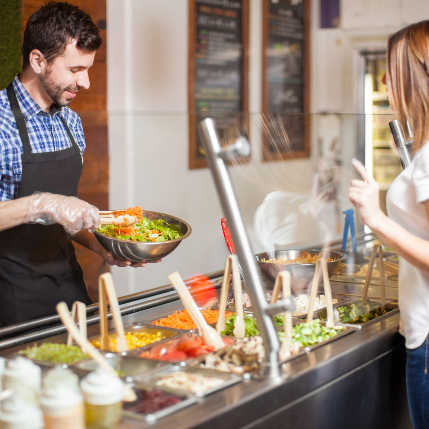 Man with a beard making a salad for a customer at restaurant - Food Shield Certification Requirements | NSF International