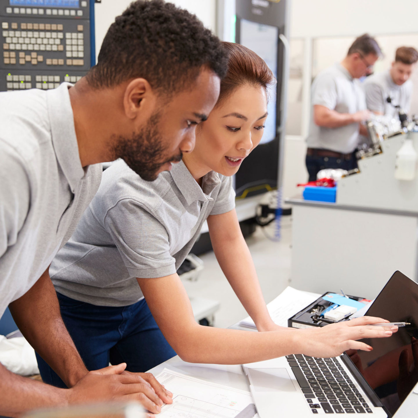 Man and woman working together pointing at a laptop