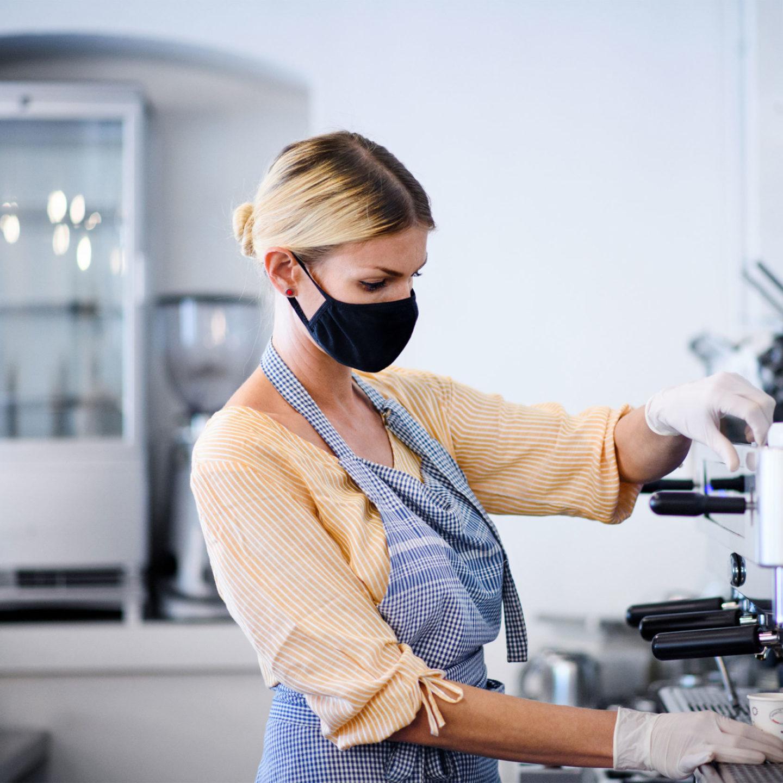 Masked barista working at an espresso machine