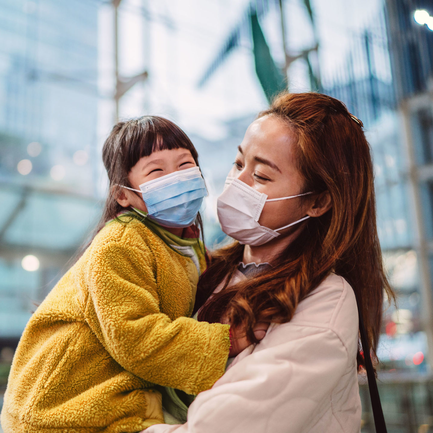 Mother holding daughter while both are wearing masks