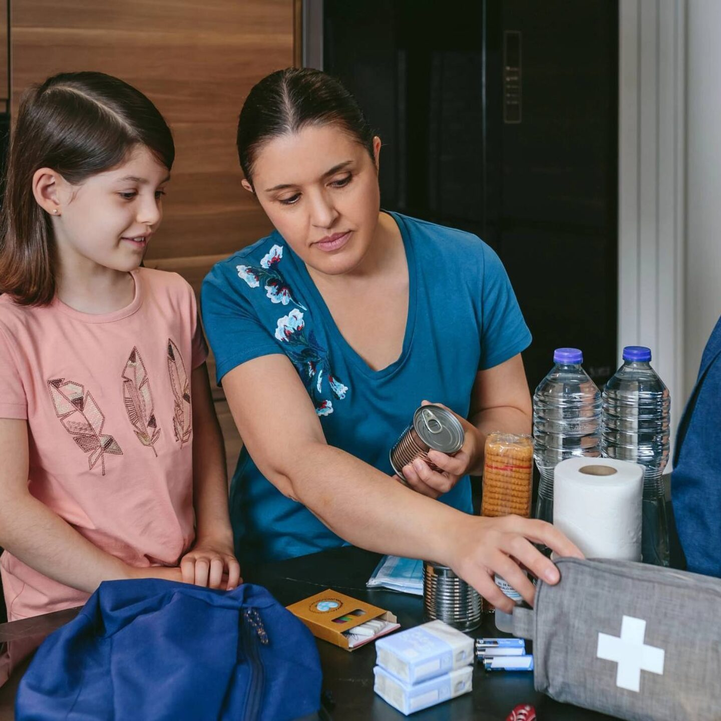 Mother and daughter filling backpack - Be Ready with Our Emergency Preparedness Tips | NSF International