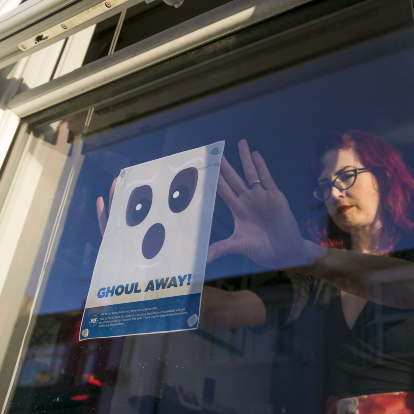 Woman hanging NSF Halloween poster in window