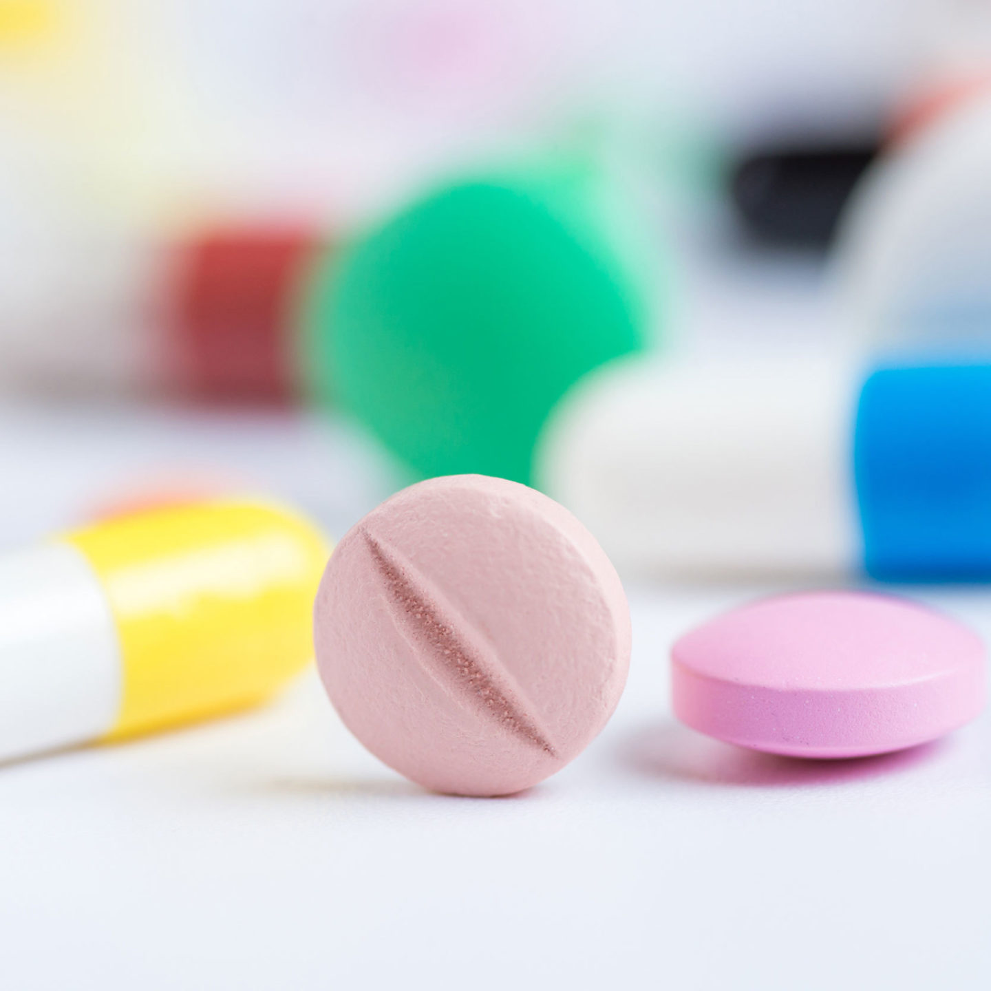 Green, pink, blue and yellow pills or capsules on a white background