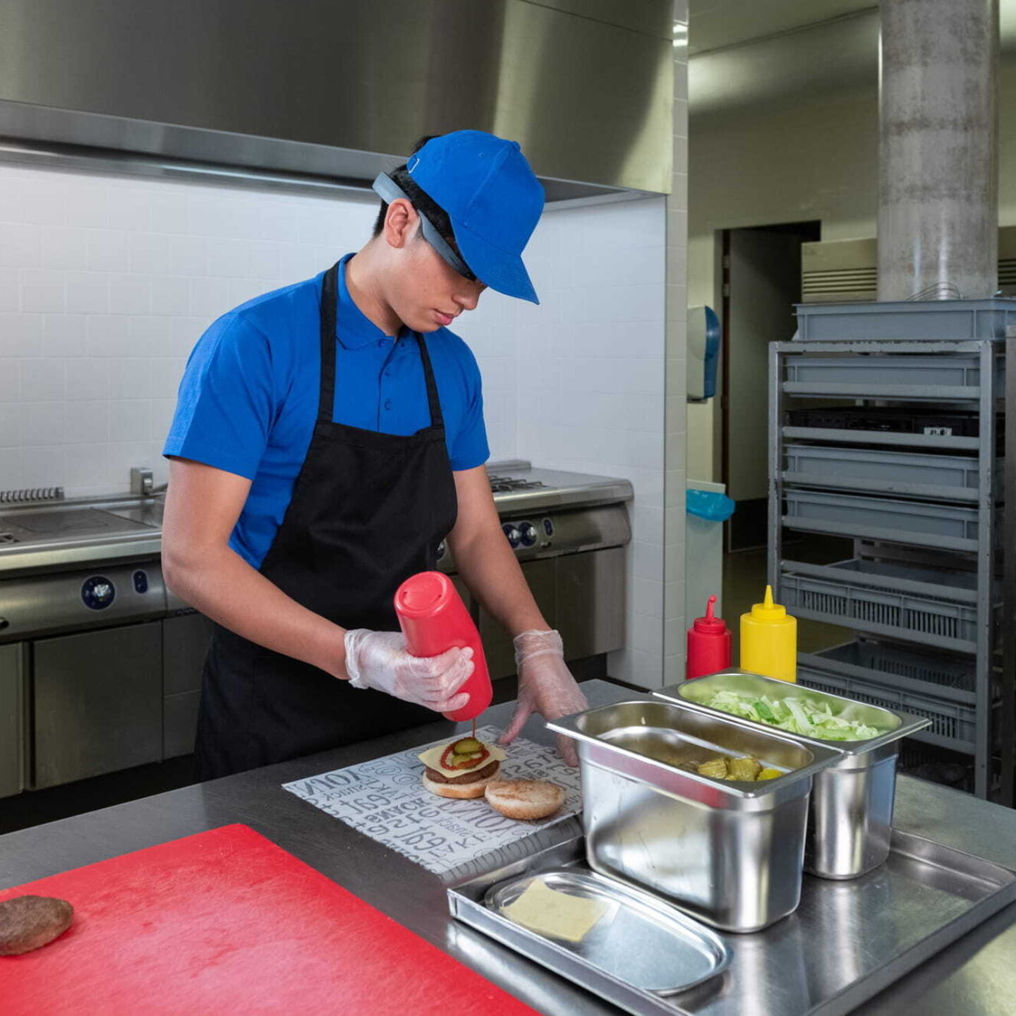 A restaurant worker adding sauce on burger patty - Wearable AR Technology for Food Service Industry | NSF International
