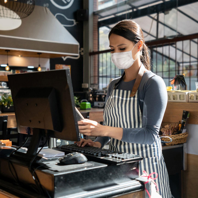 Masked restaurant worker at a register