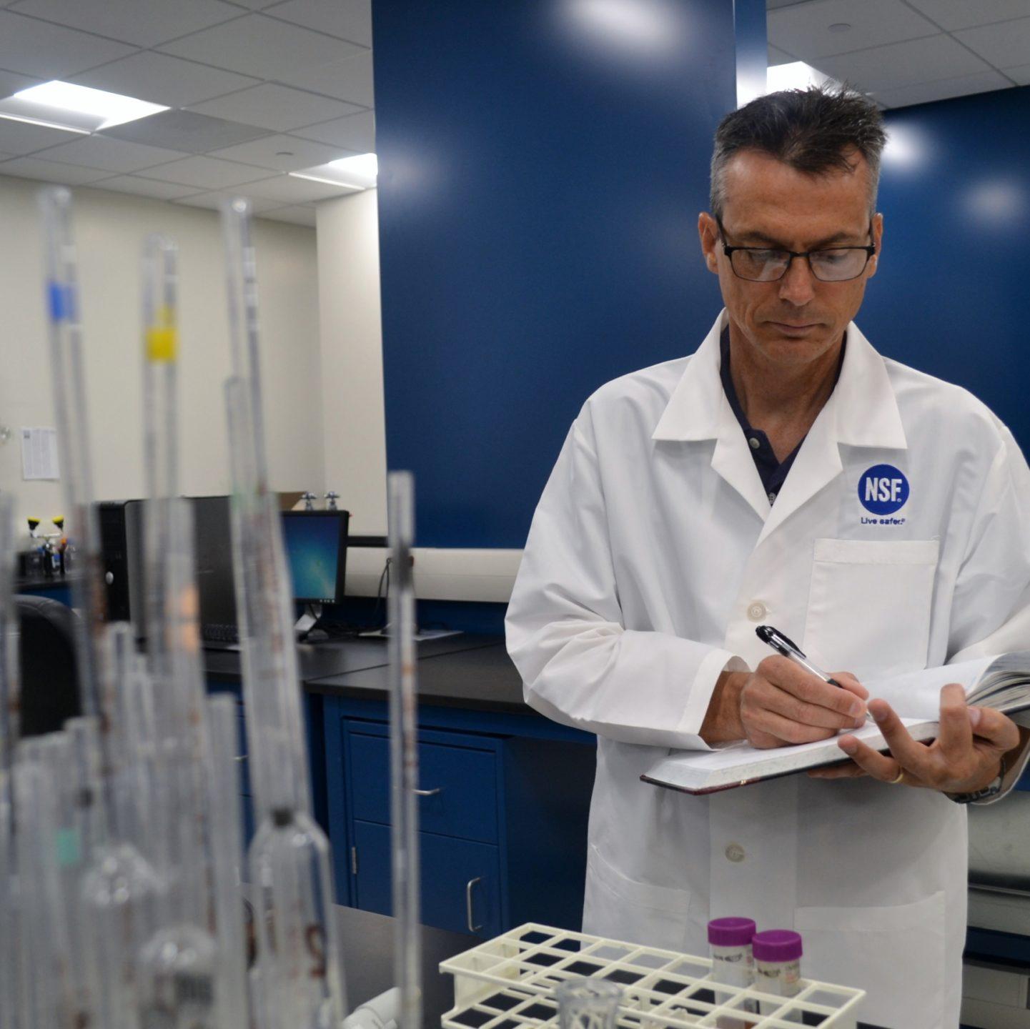 John Travis on notebook in lab