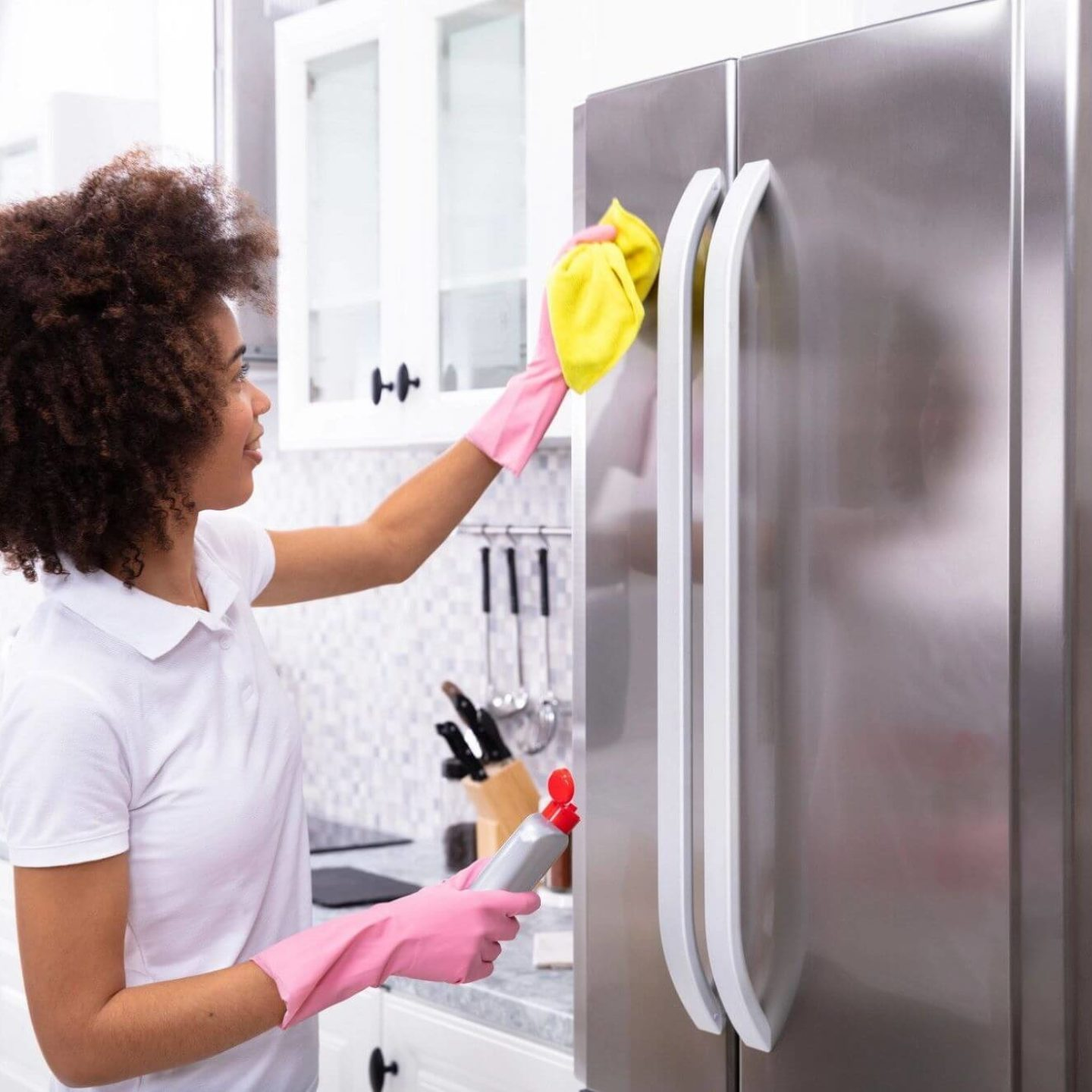 Woman cleaning refrigerator - Spring Cleaning to Feel Better and Create a Healthier Home   NSF International