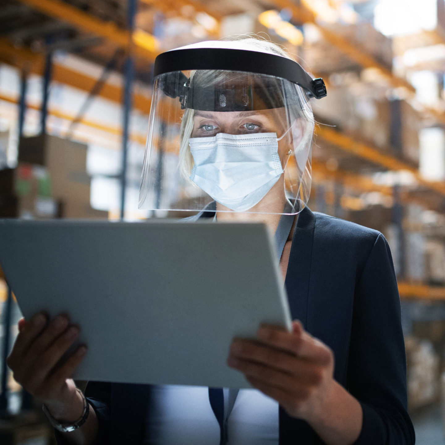 Woman wearing a face shield and mask while reading a tablet