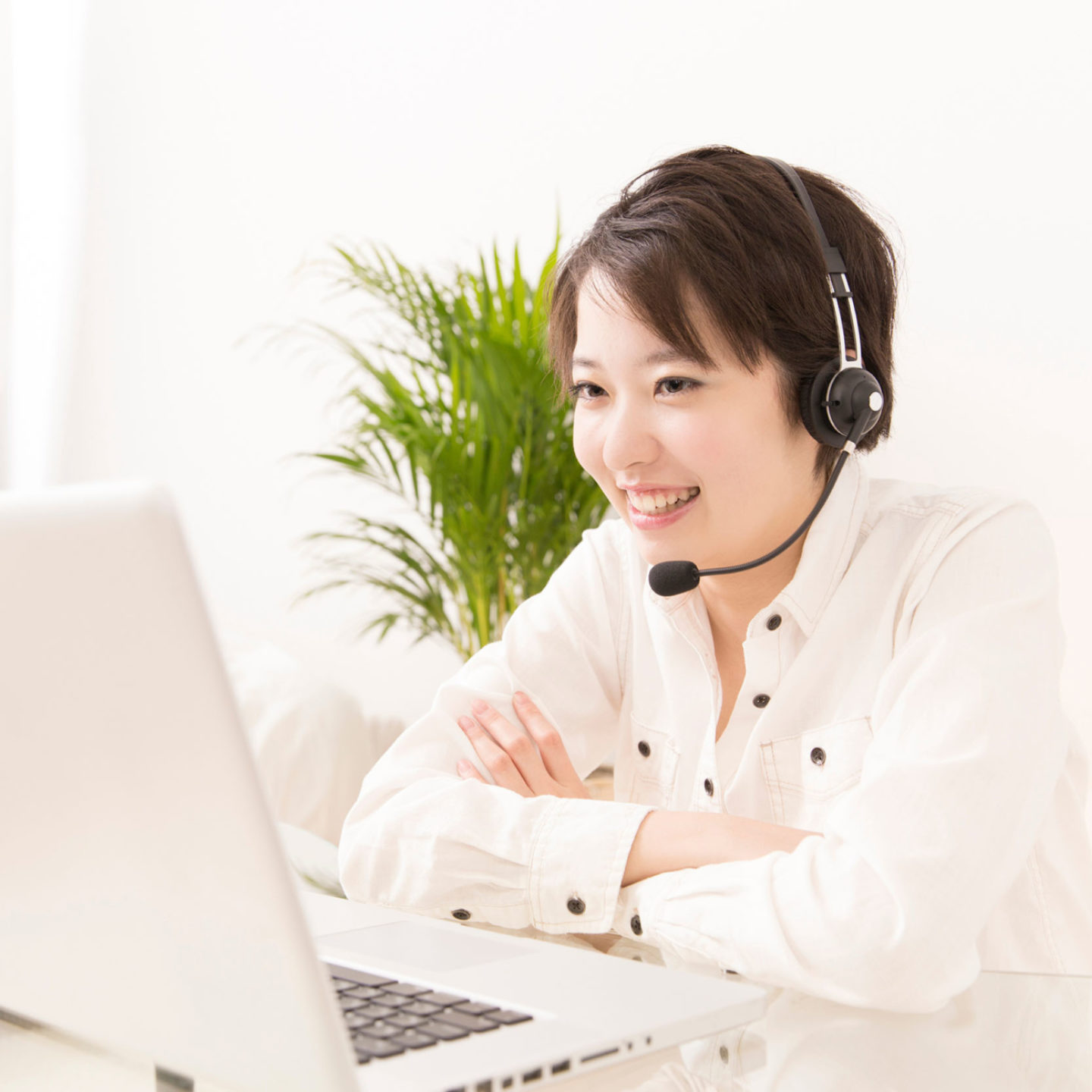 Woman on headset smiling at laptop