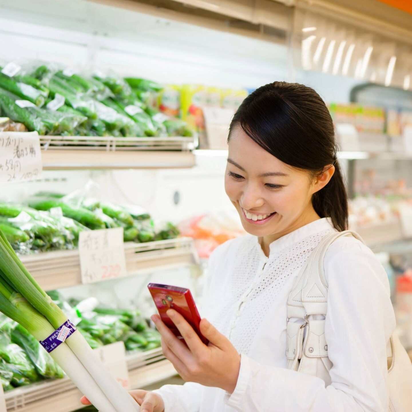 Woman looking at smartphone during grocery shopping - Three Tips to Shop for Plant-Based Food | NSF International