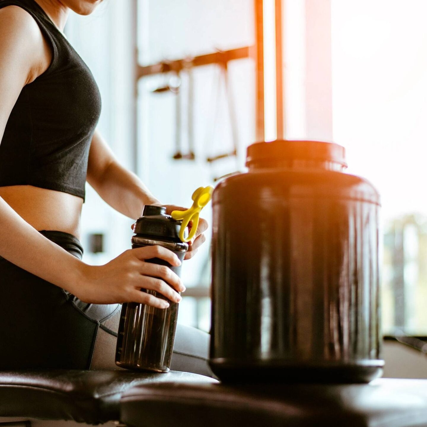 Woman at gym drinking protein water from bottle - Beware of Heavy Metals present in Sports Supplements | NSF International