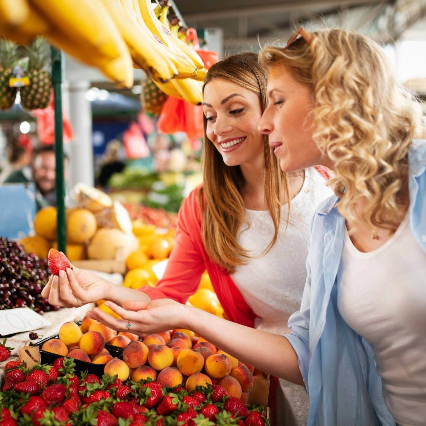 Happy young women shopping fruits in the market - Clear the Confusion About Organic and Non-GMO Food   NSF International