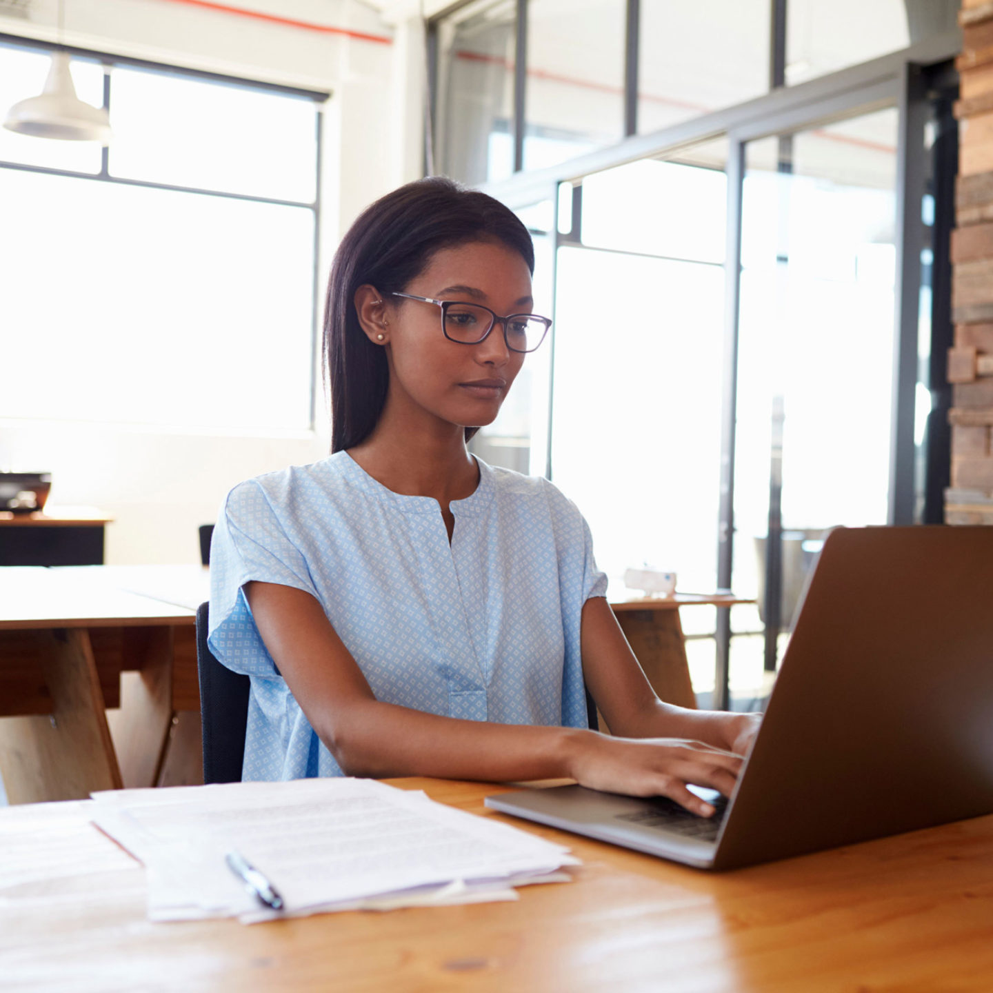 Young black woman working in office with laptop computer