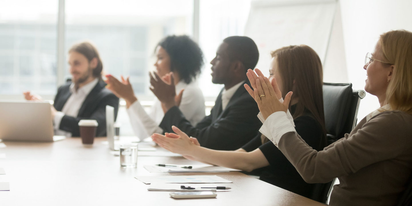 Business people applauding sitting at conference table