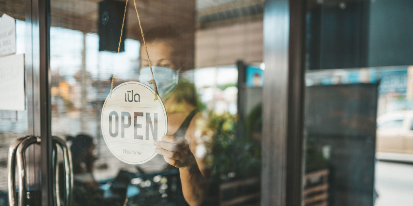 Business Owner Turning Sign to Open - Operating Your Business During COVID-19 | NSF International
