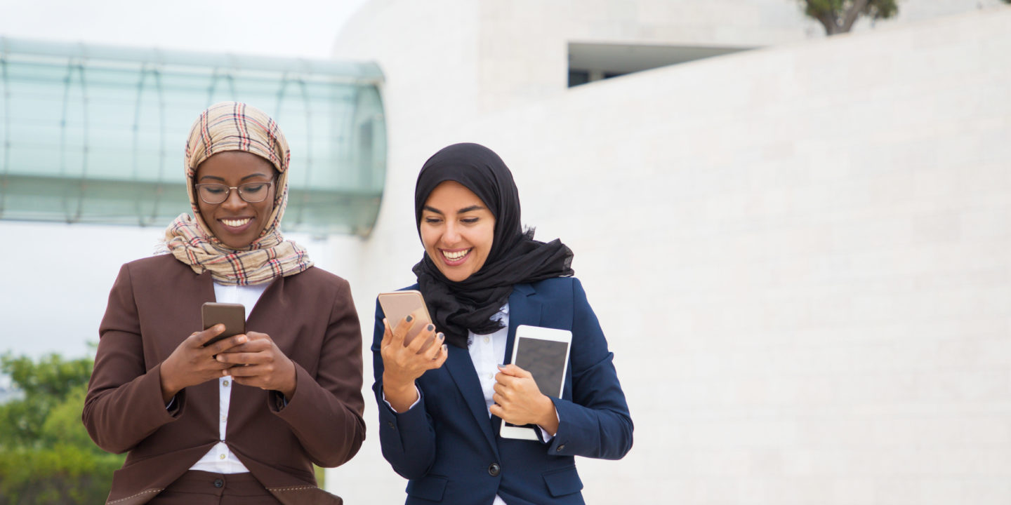 Business women smiling while using mobile devices