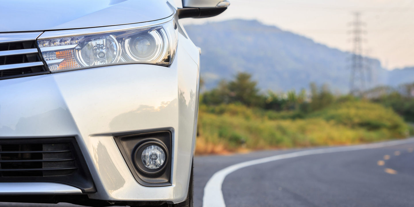 Close up front of silver car on road with hills in the background