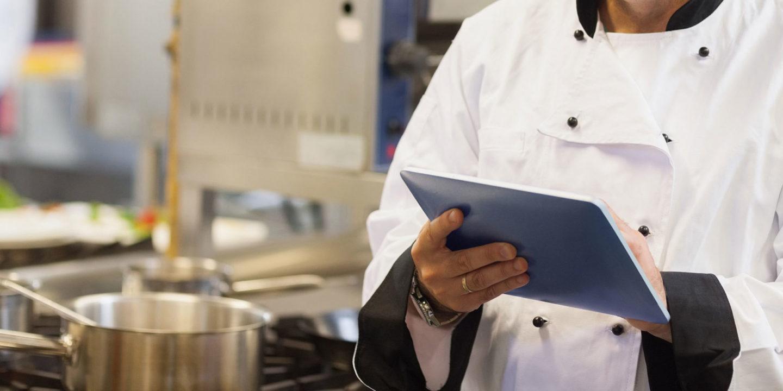 Chef checking restaurant data on a tablet - TraQtion   NSF International