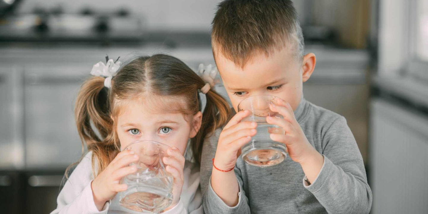 Children drinking water in kitchen - Finding the Best Water Filter for Your Home | NSF International