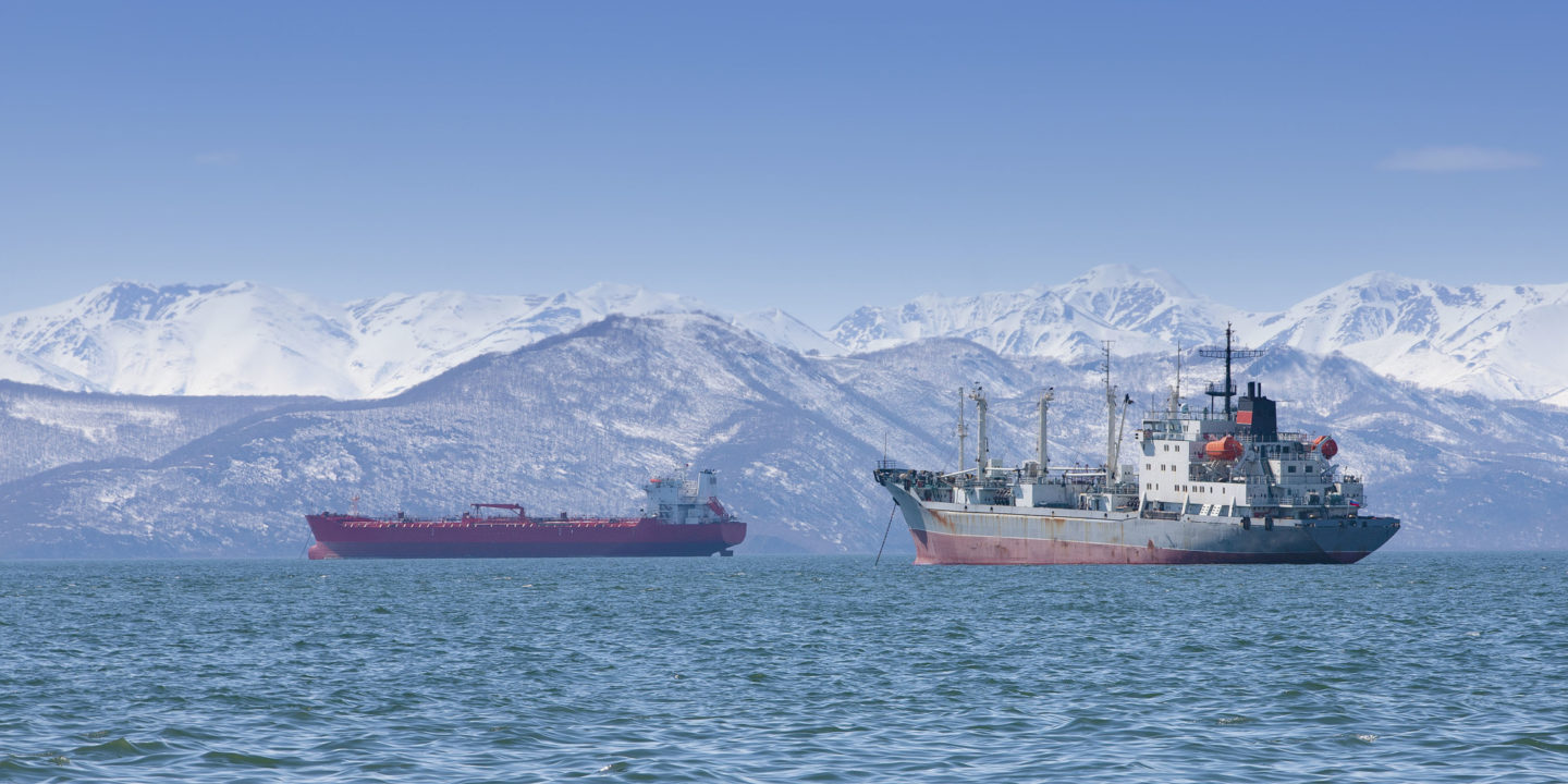 Commercial fishing boats in front of mountains | NSF International